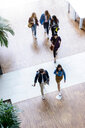 Male and female university students walking and talking in university lobby, high angle view - CUF44356