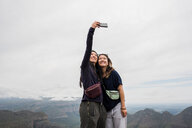 Two young female tourists taking selfie from The Three Rondavels, Mpumalanga, South Africa - CUF44392