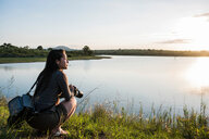 Young female tourist looking out over river in Kruger National Park, South Africa - CUF44395