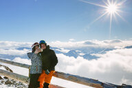 Skiing couple taking smartphone selfie above the clouds, Madonna di Senales, Trentino-Alto Adige, Italy - CUF44425