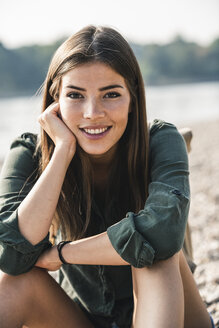 Portrait of smiling young woman sitting outdoors - UUF15318