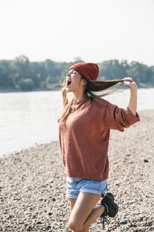 Carefree young woman screaming at the riverside - UUF15354