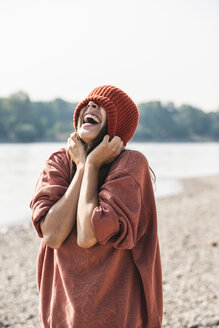 Carefree young woman wearing wooly hat at the riverside - UUF15357
