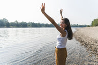 Happy young woman standing at the riverside raising her arms - UUF15372