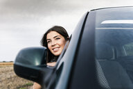 Smiling young woman leaning out of car window - UUF15414