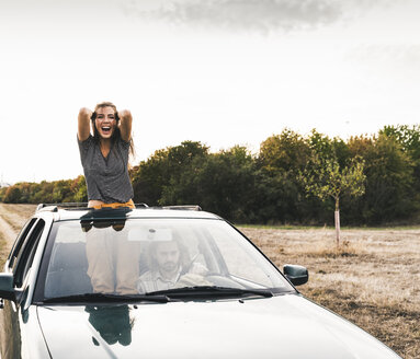 Carefree young woman looking out of sunroof of a car - UUF15420
