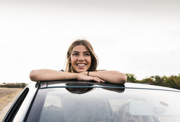 Smiling young woman looking out of sunroof of a car - UUF15423