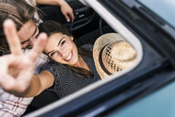 Happy young couple in a car seen through sunroof - UUF15435