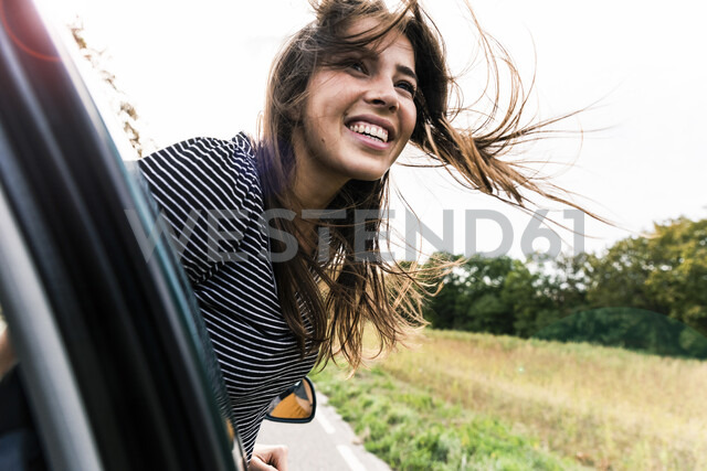Happy young woman leaning out of car window - UUF15438