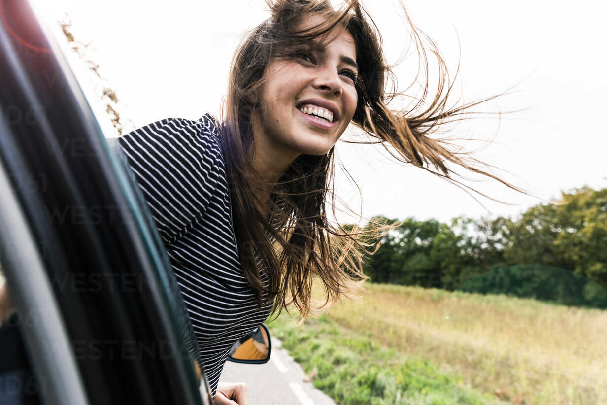 Happy young woman leaning out of car window - UUF15438 - Uwe Umstätter/Westend61