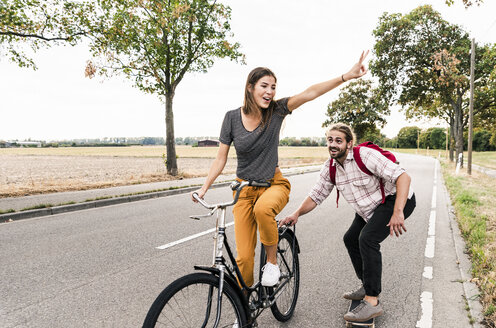 Happy young couple with bicycle and skateboard on country road - UUF15444