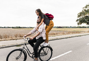Happy young couple riding together on one bicycle on country road - UUF15447