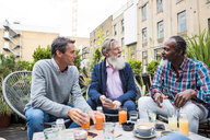 Friends chatting over drinks outdoors, London, UK - CUF44484