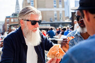 Friends having pizza at food market, London, UK - CUF44487