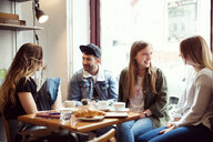 Friends chatting over coffee in cafe - CUF44526