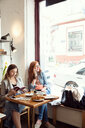 Women reading and chatting on mobile phone in cafe - CUF44529