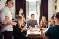 Group of friends chatting over drinks and pizza at home - CUF44541