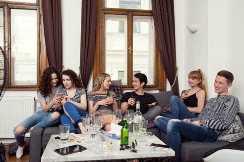 Group of male and female adult friends sitting on sofa chatting and drinking - CUF44565