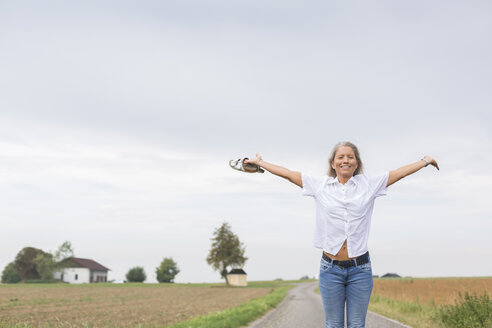 Mature woman standing on remote country lane in summer with outstretched arms - JUNF01439