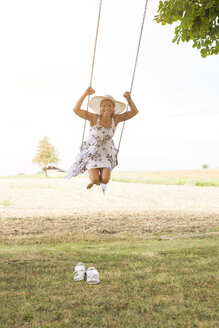 Happy mature woman on swing in remote countryside - JUNF01442