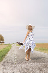 Mature woman standing on remote country lane in summer - JUNF01445