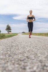 Mature woman running on remote country lane in summer - JUNF01457