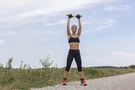Mature woman doing workout on remote country lane in summer - JUNF01460