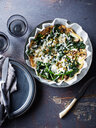 Still life with bowl of spinach feta mushroom frittata, overhead view - CUF44634