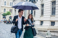 Couple with umbrella on morning commute, Budapest, Hungary - CUF44724