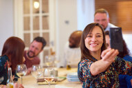 Friends taking selfie at dinner party - CUF44733