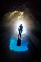 Woman free-diving, low angle view, Swallow Cave, Vavau, Tonga, Fiji - CUF44838
