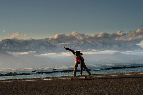 Young boy skateboarding along coastal road, Kaikoura, Gisborne, New Zealand - CUF44871