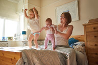Woman on bed playing with baby and toddler daughters - CUF44907
