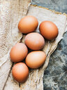 Fresh brown eggs on cloth, overhead view - CUF44940