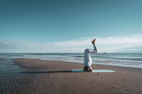 Woman practising yoga on beach - CUF44991
