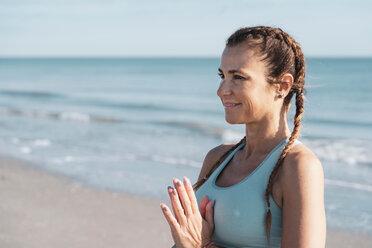 Woman practising yoga on beach - CUF44994