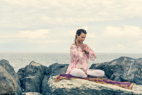 Woman meditating by sea - CUF45000