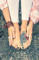 Woman touching tattooed feet with hands - CUF45003