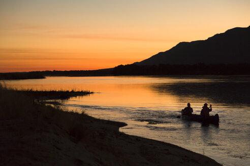 Tourists on canoe safari at sunset on lower Zambezi River in Zambia - LUXF00853