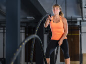 Athletic young woman exercising with battle ropes at gym - STSF01752