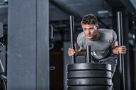 Athletic young man exercising with weight sled at gym - STSF01755