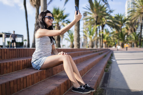 Spain, Barcelona, young woman sitting on steps at sunlight taking selfie with smartphone - GIOF04611
