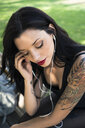 Portrait of young woman with nose piercing and tattoos listening music with earphones - GIOF04656