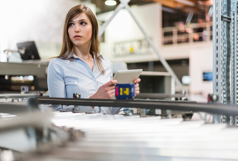 Young woman in factory, holding digital tablet, looking away - CUF45082