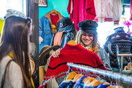 Friends browsing vintage clothes in thrift store - CUF45085