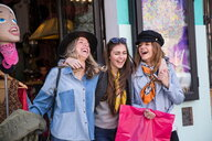 Friends leaving clothing shop smiling - CUF45088