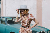 Woman wearing hat by vintage car - CUF45094