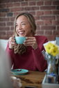 Woman sitting in cafe, drinking coffee, smiling - CUF45115