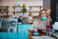 Woman sitting in cafe, holding smartphone, drinking coffee - CUF45121