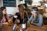 Three young female friends with vegetable juice chatting in cafe - CUF45133